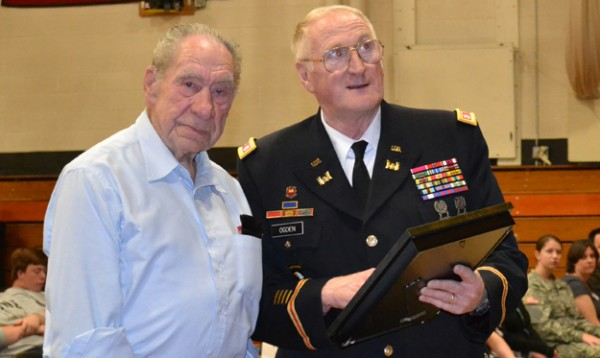 Maine Bureau of Veterans' Services Director Peter Ogden (right) presents U.S. Navy veteran Chet Crocker with his World War II medals at Wiscasset High School on June 6.