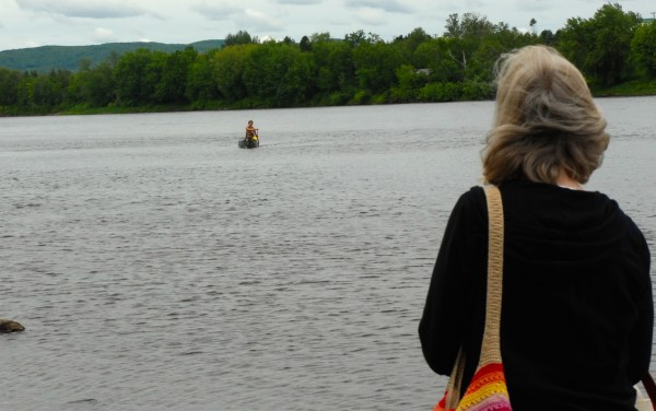 Laurie McIntyre stands on the banks of the St. John River in Fort Kent as her son Eric completes the final few yards of the 740-mile Northern Forest Canoe Trail which began in Old Forge, New York.