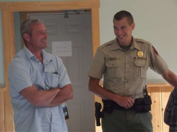 Tracey Sawtelle (left), a fisherman from Lubec, and state Marine Patrol Officer Brian Brodie (right) share a light moment after a meeting of scallop fisherman in Dennysville on Tuesday afternoon.
