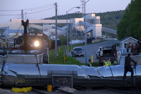 A tow truck operator (far right) checks a towline attached to a tanker truck that had been hit by a train at the Verso Paper Co. mill's north gate on Saturday.