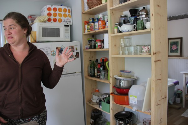 Jennifer Jacques shows on Saturday how the walls in her 'itty bitty' Orland home were turned into shelves to save space.