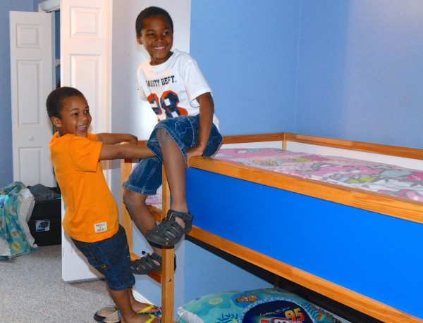 Six-year-old Jacoby, left, horses around with his 7-year-old brother Judah in the bedroom of their new St. Francis home.
