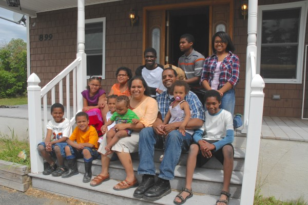 All 13 members of the Jerome and Joyce Jackson family take a moment to relax together on the porch of their new St. Francis home. The family was able to purchase the house thanks to a program through USDA Rural Development.