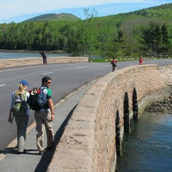 Hikers walk along a causeway on the Park Loop Road that crosses Otter Cove in Acadia National Park.