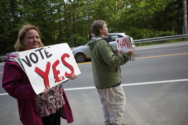 From left, Peggy Merritt and Julie Beckford of Rebel Hill Farm wave Vote Yes signs on a referendum to increase wind farm setbacks to 4,000 feet on Election Day in Clifton, Maine.