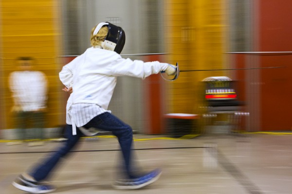 Izaak Swartz, 10, lunges towards Lily Millard, 9, during a saber match at the Downeast School of Fencing class at the Herbert Sargent Community Center in Old Town.
