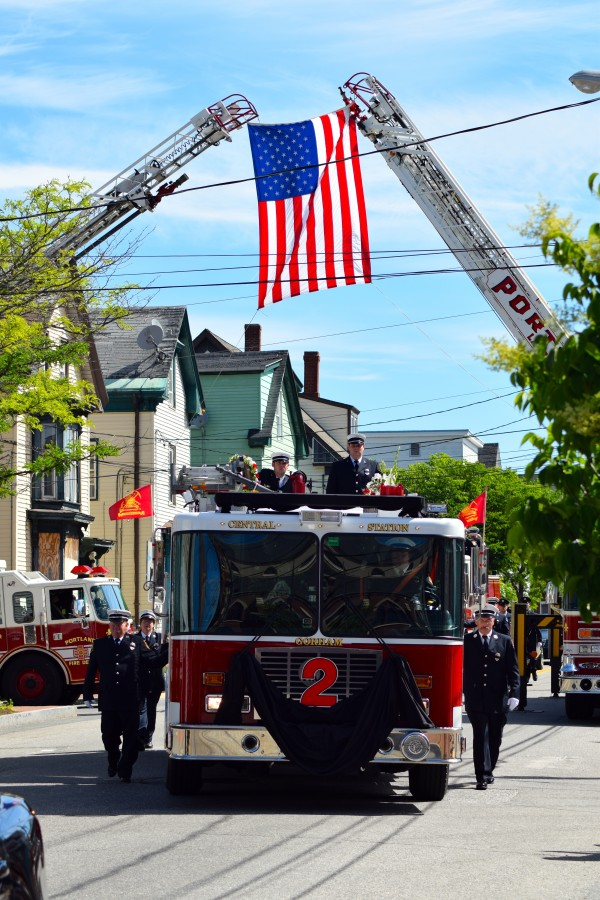 Members of the Portland Fire Department ride atop and walk beside the truck that carried Michael Kucsma's casket on Cumberland Avenue.