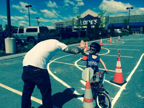 Caleb Collins, 5, from Kenduskeag gets a high-five from Lowe's employee Robert Dunphy of Plymouth after completing the obstacle course portion of a bike rodeo for kids held Saturday, June 7, 2014, in the parking lot of the retail store in Bangor.