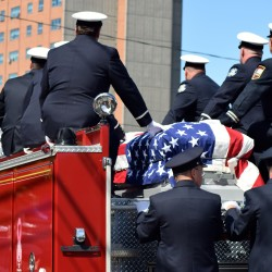 Pallbearers rode atop a firetruck with the casket during the procession.