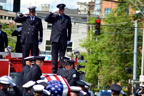 Members of the Portland Fire Department salute Kucsma's casket as it is taken off a truck by pallbearers.
