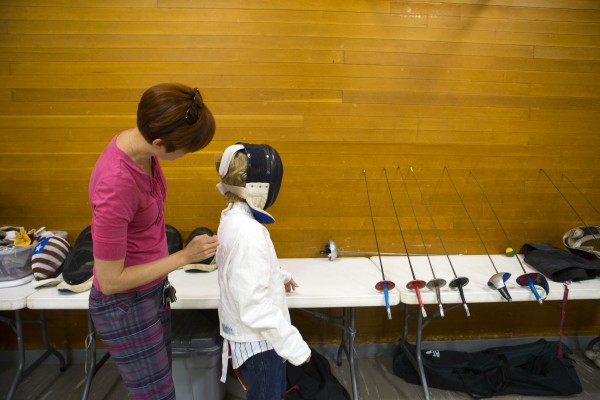 Kristin Swartz (left) helps her son, Izaak Swartz, 10, adjust his fencing gear during the Downeast School of Fencing class at the Herbert Sargent Community Center in Old Town.