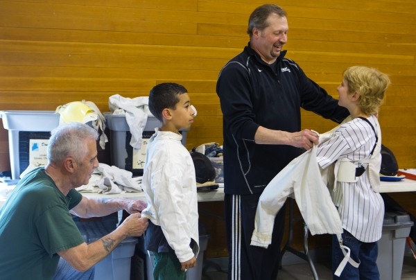 James King (left) and instructor John Krauss (second from right) help James King (second from left), 10, and Izaak Swartz, 10, into their fencing gear before practice during the Downeast School of Fencing class at the Herbert Sargent Community Center in Old Town.