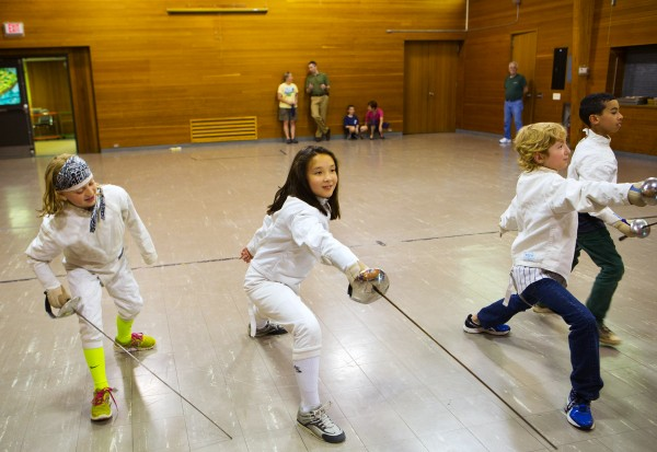 From left, Erin Gerbi, 11, Lily Millard, 9, Izaak Swartz, 10, and James King, 10, warm up with a game during the Downeast School of Fencing class at the Herbert Sargent Community Center in Old Town.