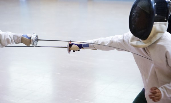 James King, 10, is attached by Izaak Swartz, 10, during a foil match at the Downeast School of Fencing class at the Herbert Sargent Community Center in Old Town.