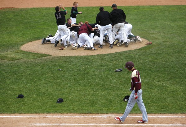 BANGOR, MAINE -- 06/21/14 -- Caribou's Mason Huck (right) walk back to his team's dugout as Greely celebrates in the background during their Class B baseball state championship game at Mansfield Stadium Saturday. Greely beat Caribou 1-0.