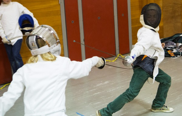 Erin Gerbi (left), 11, makes contact with James King, 10, during a foil match at the Downeast School of Fencing class at the Herbert Sargent Community Center in Old Town.