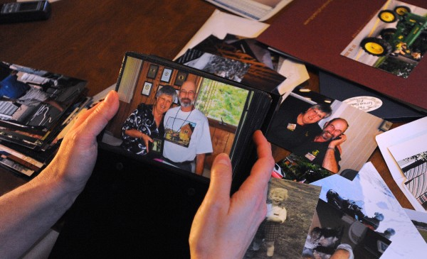 Amy Gailitis looks through photographs of her father, Wallace &quotWally&quot Fenlason, on July 5, 2013.  Wallace Fenlason died during the parade on the Fourth of July in Bangor last year.