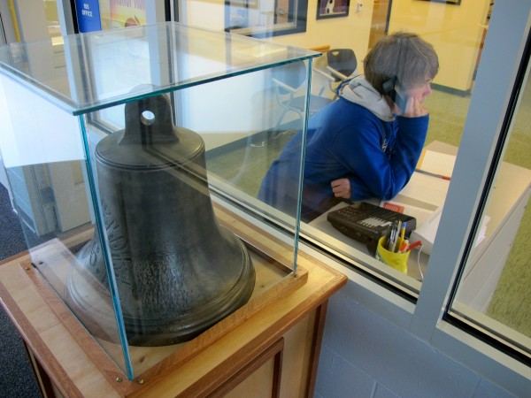 Greg Keenan, 13, uses a phone in the front office of Peninsula School in the Gouldsboro village of Prospect Harbor while an historic bell sites in a display case in the hallway.