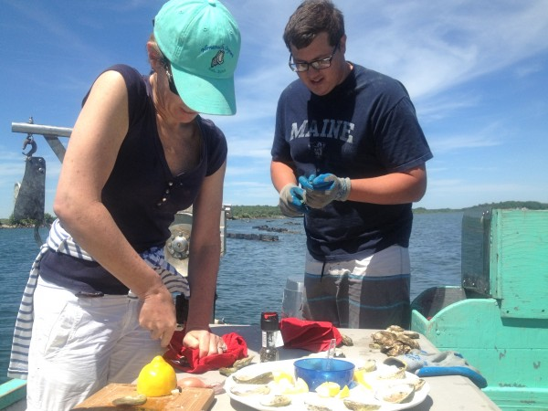 Abigail Carroll of Nonesuch Oysters and oyster farmer Luke Patry serve freshly harvested bivalves on the Scarborough River.