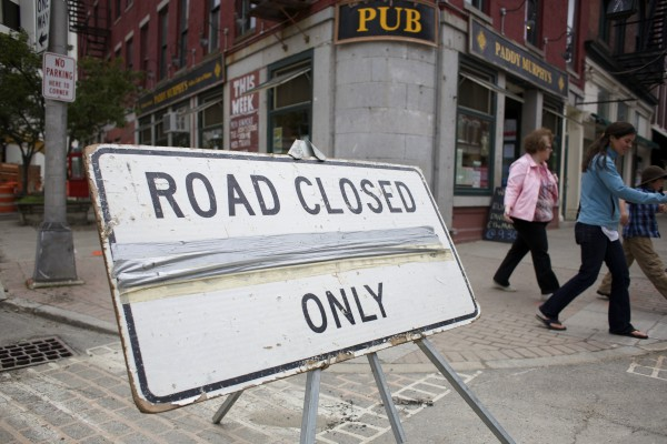 Pedestrians walk near a road closure sign blocking off Broad Street on Friday afternoon in Bangor.