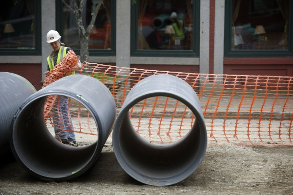 A construction worker puts up construction fencing Friday around an area of West Market Square in Bangor.