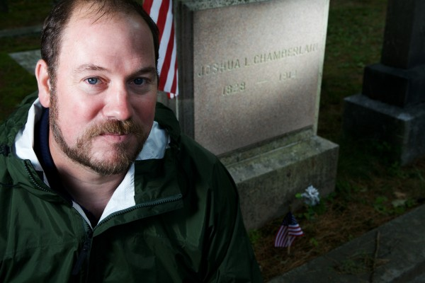 Dean Clegg sits by the grave of Joshua Chamberlain in Brunswick on Thursday. On June 18, 1864, Col. Joshua L. Chamberlain was shot through the gut while leading a Union charge against Confederate works defending Petersburg, Virginia. Clegg is raising money to mark the spot, now a residential community.