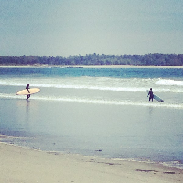 Surfers walk into Old Orchard Beach in early June in Maine.
