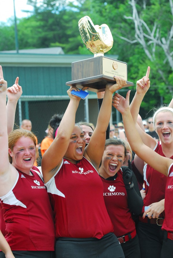 Richmond High School's Helsie Obi holds the trophy high with Kalah Patterson (left), Camryn Hurley (right) and Kelsea Anair (far right) after defeating Limestone for the Class D state softball title at Coffin Field in Brewer Saturday.
