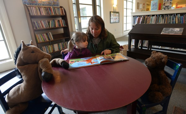 Two-year-old Lucy Nicols has a little reading party with some stuffed animals and her grandmother Kim Corriveau on Friday morning in the children's area of the Bangor Public Library.