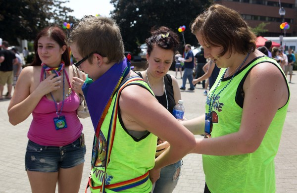 McKayla Mitchell (right) helps Tyler Hewins (second from left) with his suspenders, while Kayla Landry (left) and Tori Bruce watch during the Bangor Pride Festival.