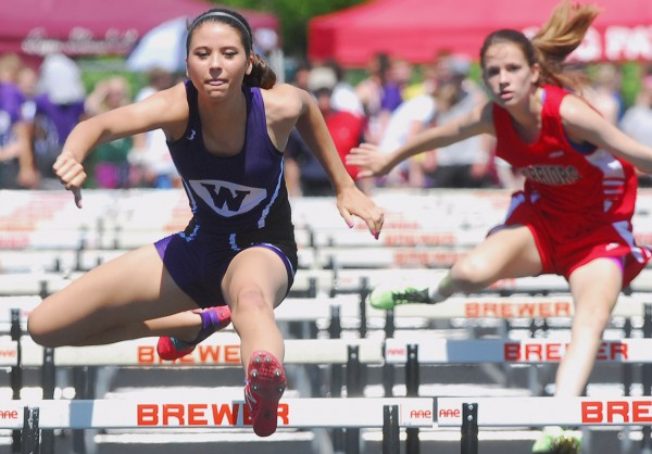 Waterville's Kellie Bolduc finishes first just a head of Emily Cottis of Wells during the 2nd Heat of the 100-meter hurdles at the 2014 Class B Track and Field Championship Meet at the Brewer Community Track on Saturday.