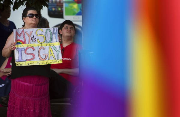 Alice Nadau (left) holds up a sign in support of her gay son Sean West (right) during the Bangor Pride Festival on Saturday at Pickering Square in Bangor.