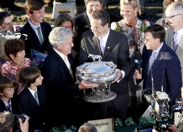 Robert Evans, owner of Tonalist, accepts the Belmont Stakes Trophy from New York Gov. Andrew Cuomo (center) at the 146th running of the Belmont Stakes at Belmont Park in Elmont, New York, on June 7, 2014.