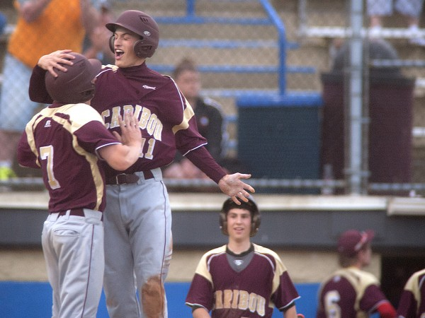 Caribou's Mason Huck (11) celebrates with teammate Dylan Berkoski (7) after scoring a run in the sixth inning of their Eastern Maine Class B championship against Old Town at Mansfield Stadium in Bangor, Maine, Wed., June 18, 2014. Caribou won 4-3 in 10 innings.