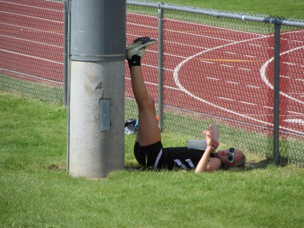 Brewer senior Synclaire Tasker finds respite from the sun in the shade of a light pole while waiting for her turn during the triple jump competition in Saturday's Class A state meet in Windham. She won the event and also took the 100- and 300-meter hurdles to help the Witches finish third.