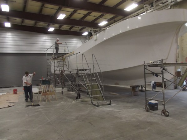 Workers at Millennium Marine clean up after a day spent building boats at the company's new shop in Eastport. Company president and CEO Cory Guimond is on top of scaffold. Guimond expanded from Canada and began operations in Maine a little over a month ago.