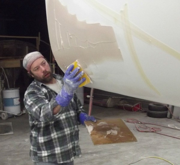 Al Morin applies composite material to the hull of a boat under construction at  Millennium Marine's new shop in Eastport. The company expects to build about 10 boats the first year and as many as 40-50 annually within three years.