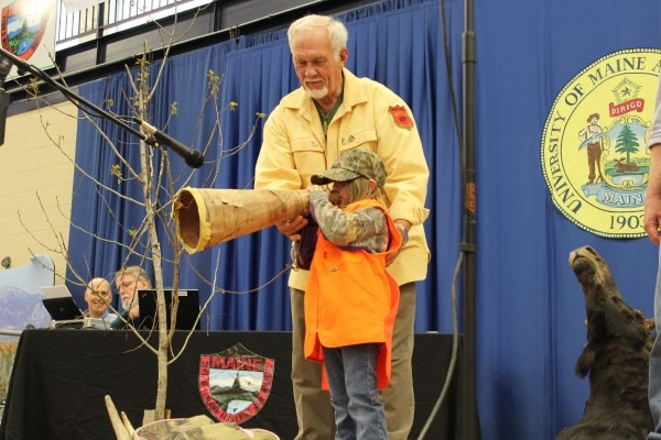 Raquelle Sterris, 5, of Fort Kent demonstrates her moose-calling skills while being coached by her grandfather, John Graves, of Presque Isle during the Maine Professional Guides Association's state championship moose-calling contest in Presque Isle on Saturday.