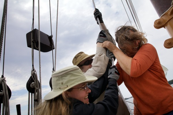 Jennifer (from left) Tom and Doris Smith hoist a sail aboard the schooner Eastwind in Boothbay Harbor on Wednesday. Doris and her husband Herb sailed around the world twice with their three children. Now their son Tom and his wife Jennifer operate the Eastwind for tourists.