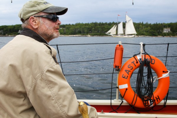 Herb Smith sails the schooner Eastwind past a wooden sailboat in Boothbay Harbor on Wednesday.