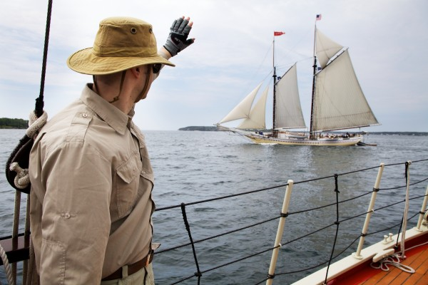 Tom Smith waves to the Heritage from aboard the Eastwind in Boothbay Harbor on Wednesday.