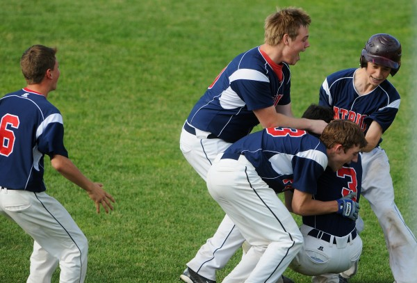 Bangor Christian's Cody Collins (3) is mobbed by teammates including (from left) Dean Grass, Kyle Holmes, Seth Pearson and Zac Palmeter after Collins' single lifted the Patriots to the Class D baseball state championship in the eighth inning at Mansfield Stadium in Bangor on Saturday.