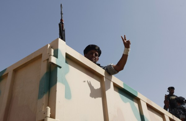 A Shiite volunteer, who has joined the Iraqi army to fight against the predominantly Sunni militants from the radical Islamic State of Iraq and the Levant (ISIL) who have taken over Mosul and other northern provinces, gestures from a truck in Baghdad on Wednesday.