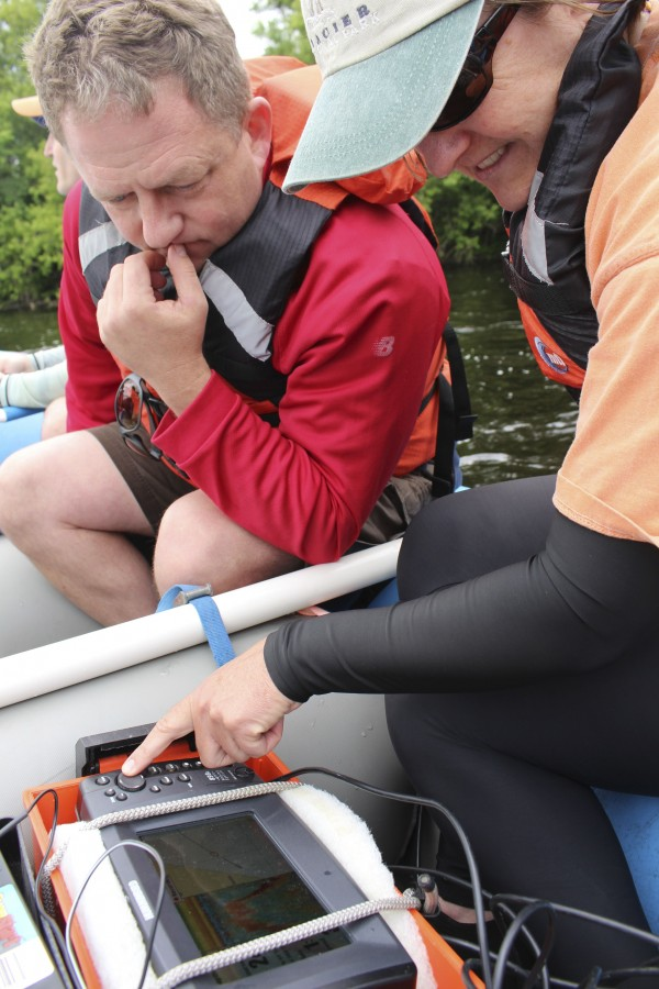 Sean Smith (left), assistant professor at the UMaine School of Earth and Climate Sciences, and Gayle Zydlewski, associate professor at the UMaine School of Marine Science, view the screen of a Humminbird fish finder on Friday on the Penobscot River. They are using it to map the substrates on the bottom of the Lower Penobscot River.