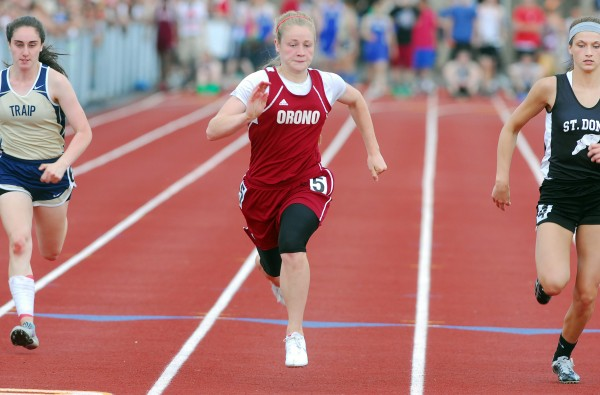 Orono's Lauren Stoops (center) finishes first in the 100-meter dash with a time of 12.88 seconds during the Class C state track and field championships Saturday at Foxcroft Academy. Stoops also won the 200 and finished third in the 400 to help Orono capture the state title.