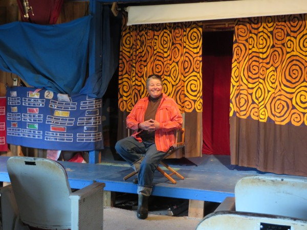 Mari Abercrombie, director of Windover Art Center, sits on the stage in Windover's Birch Tree Theater, where students have daily assemblies and present final performances at the end of each week, in June in Newburgh.