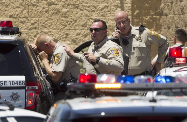 Las Vegas police report outside a Wal-Mart after a shooting in Las Vegas on June 8, 2014.  Las Vegas police said that  officers were targeted in the shooting, which left three people dead, including both shooters.