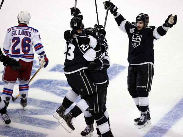 Los Angeles Kings' Dustin Brown (second left) celebrates his game-winning goal with teammates Willie Mitchell (second right) and Slava Voynov as New York Rangers' Martin St. Louis skates away during the second overtime period in Game 2 of their NHL Stanley Cup Finals  series in Los Angeles Saturday night.