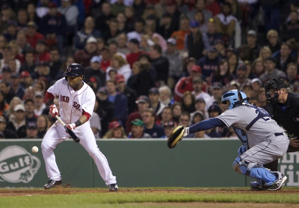 Boston Red Sox second baseman Jonathan Herrera (10) bunts to drive in a run against the Tampa Bay Rays in the fourth inning at Fenway Park in Boston Saturday night.