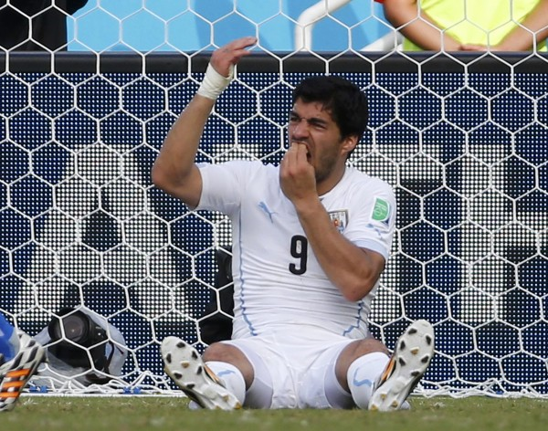 Uruguay's Luis Suarez holds his teeth during the 2014 World Cup Group D soccer match between Uruguay and Italy at the Dunas arena in Natal in this June 24, 2014 file photograph. Uruguay striker Suarez was banned for nine matches by FIFA on June 26, 2014 after being found guilty of biting Italian defender Chiellini on June 24, 2014.